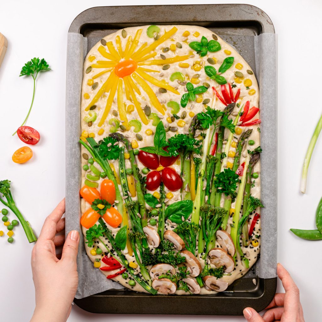 Hands holding tray with focaccia decorated with vegetables spring garden broccoli tomatoes
