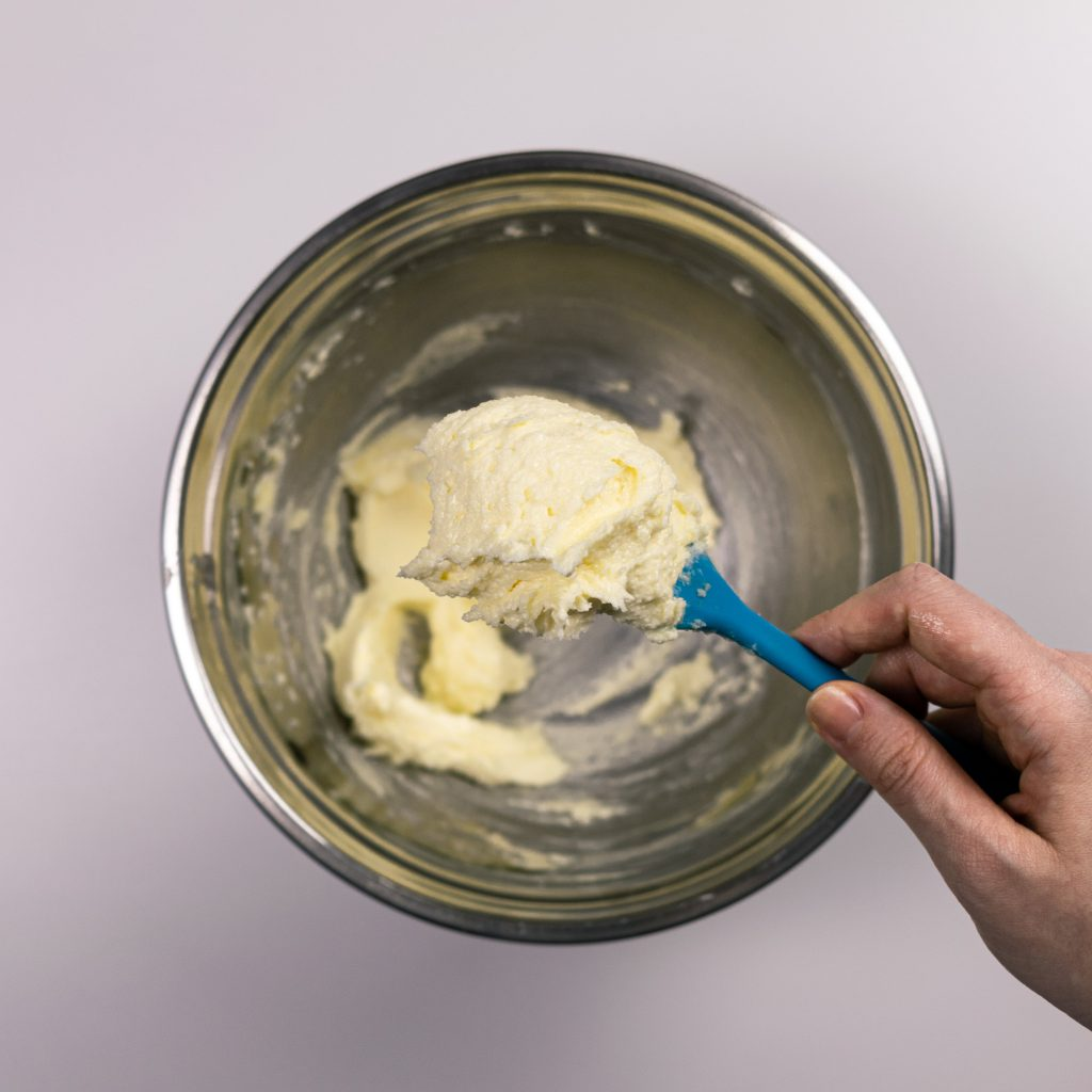 Hand holding spatula with softened butter and sweetener