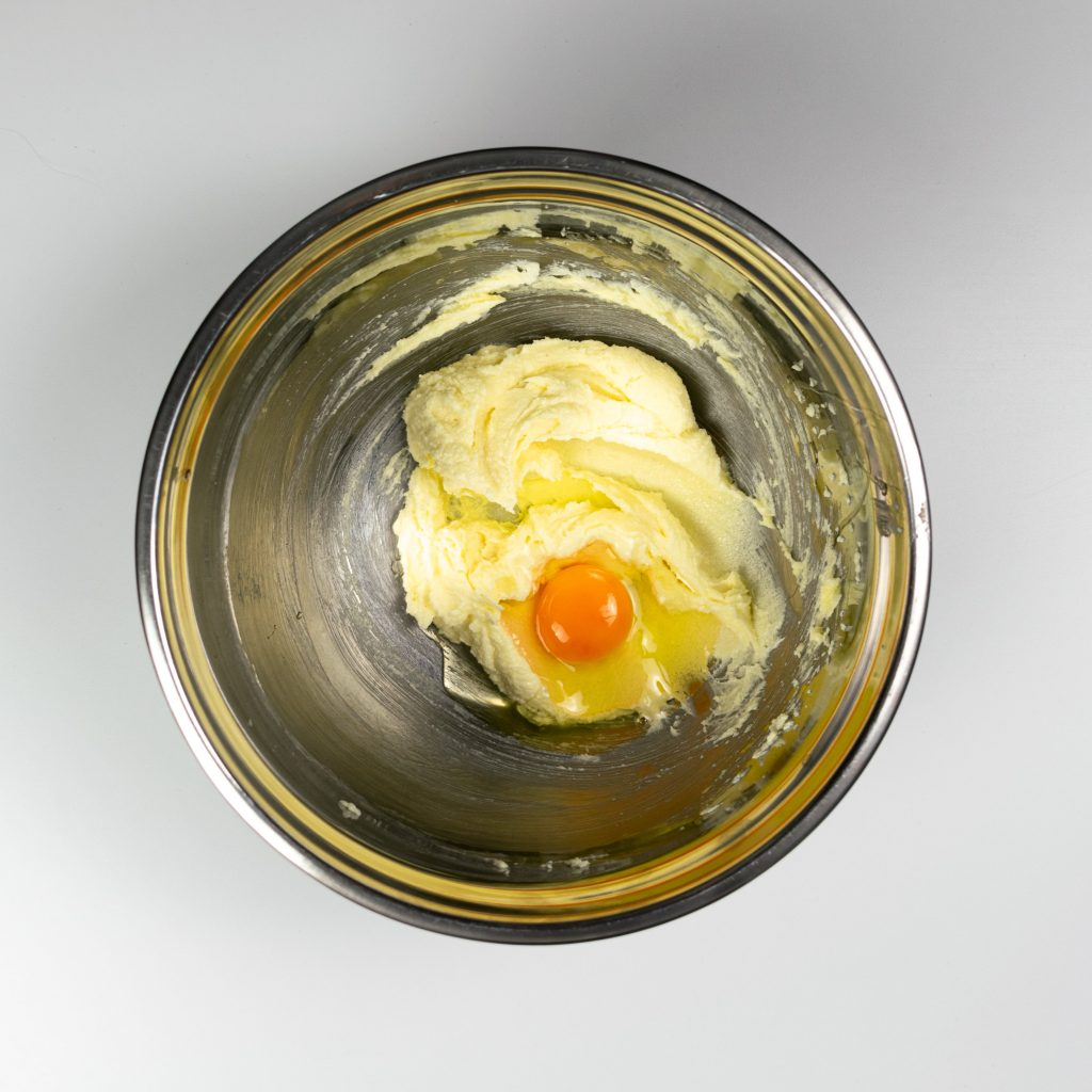 Large bowl with whipped butter and an egg