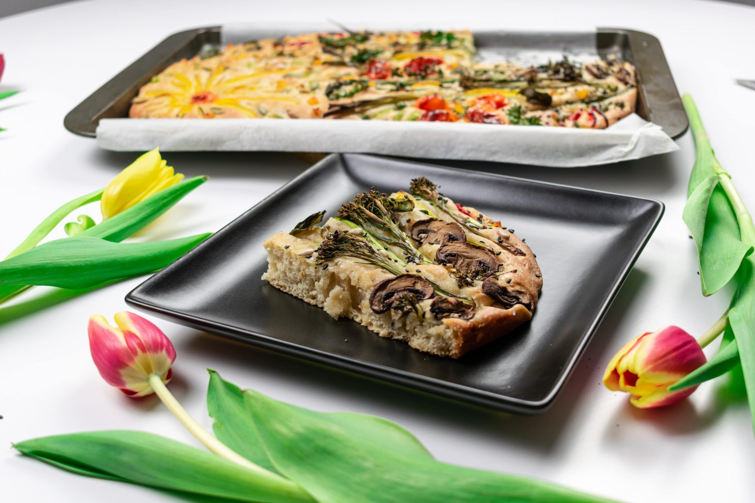 Slice of vegetable focaccia on black plate with flowers