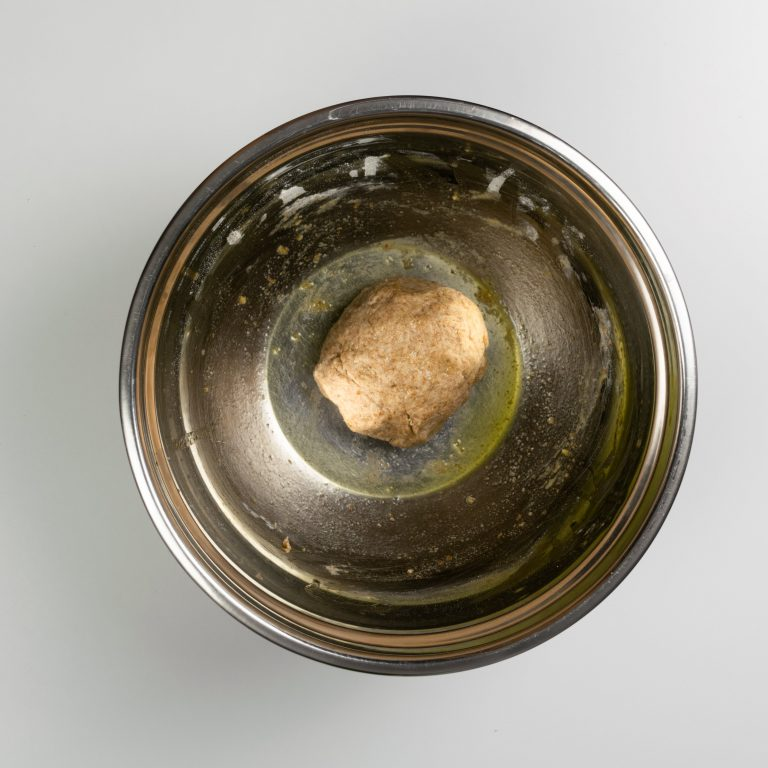 Dough kneaded into ball inside large bowl
