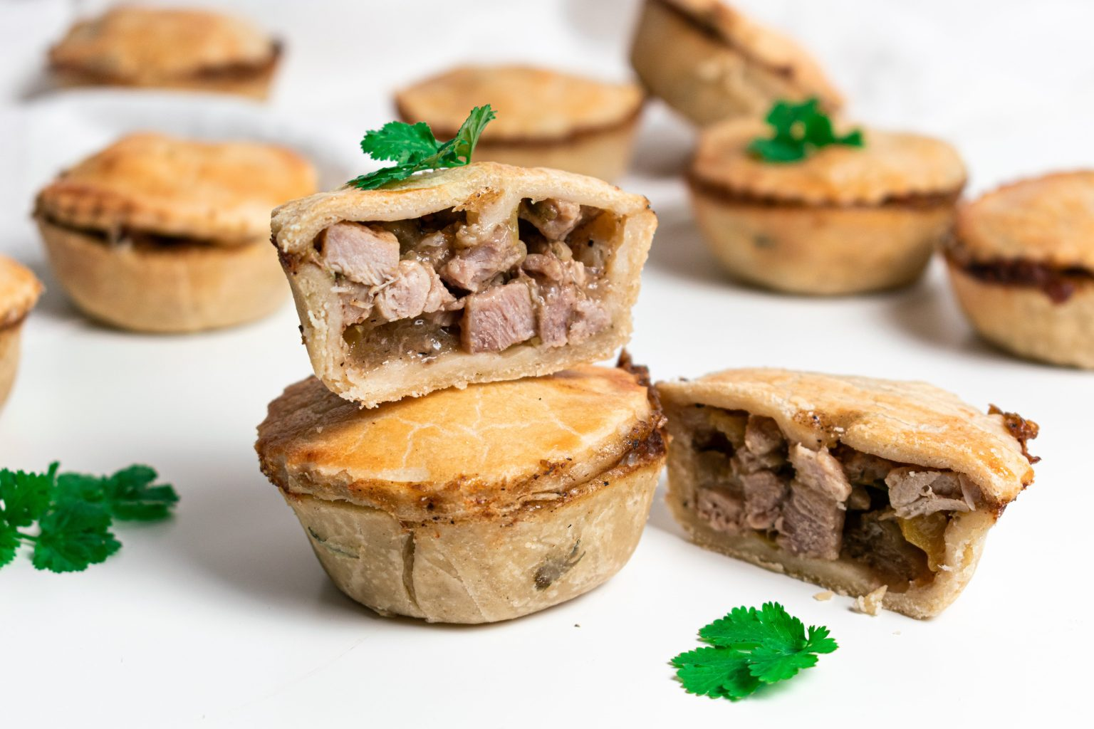 Stacked British pork pies with top pie cut into half to see pork filling