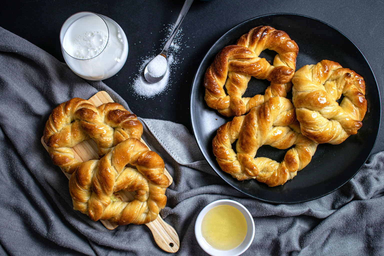 Top photo of sweet pretzels on black background with glass of milk, cup of honey and cup of sugar