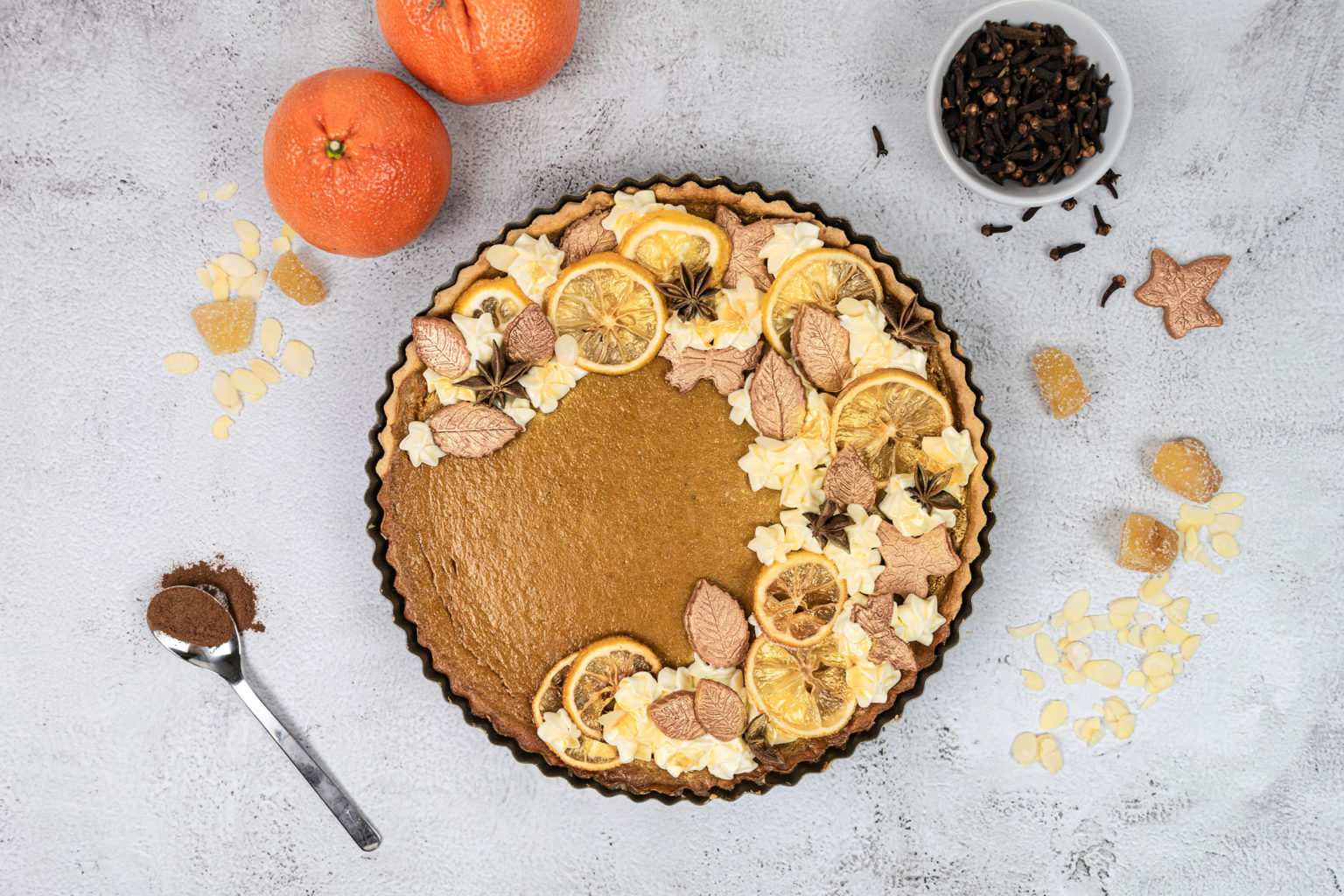Flatlay of pumpkin pie with oranges, cloves and spoon of cinnamon
