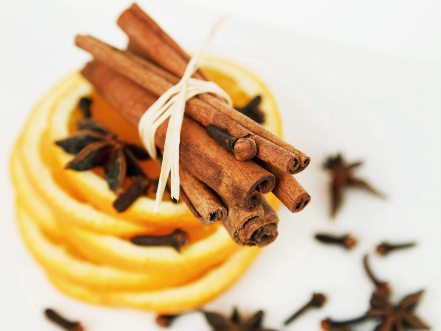 Cinnamon sticks on top of slices of orange with star anise and cloves