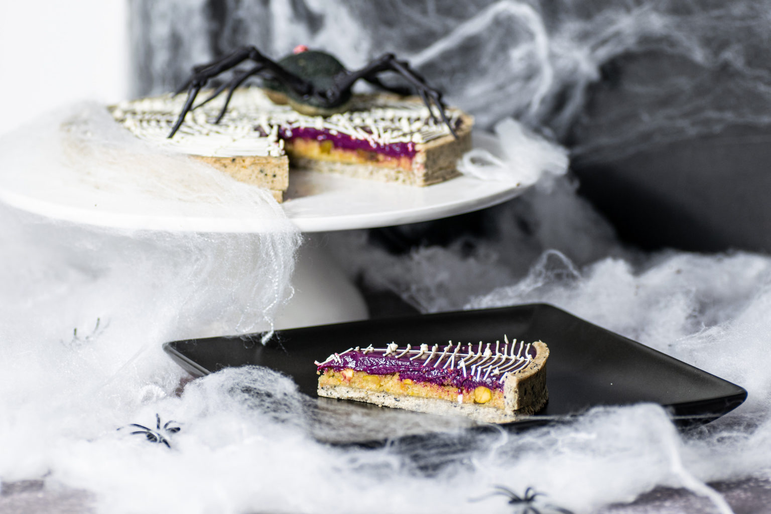 Slice of Halloween tart on plate with spiderweb tart in background and spiderwebs