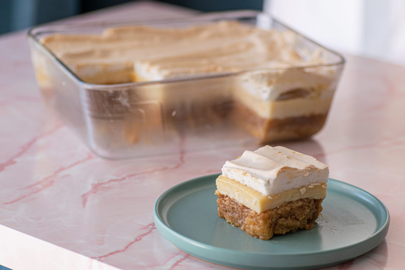 Slice of apple meringue cake with tray of cake in background