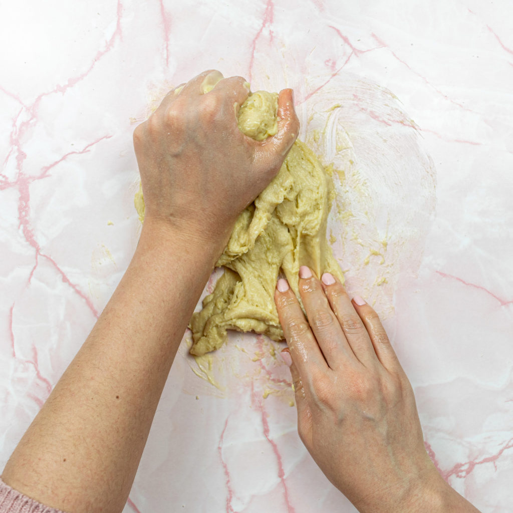 Two hands kneading dough with butter