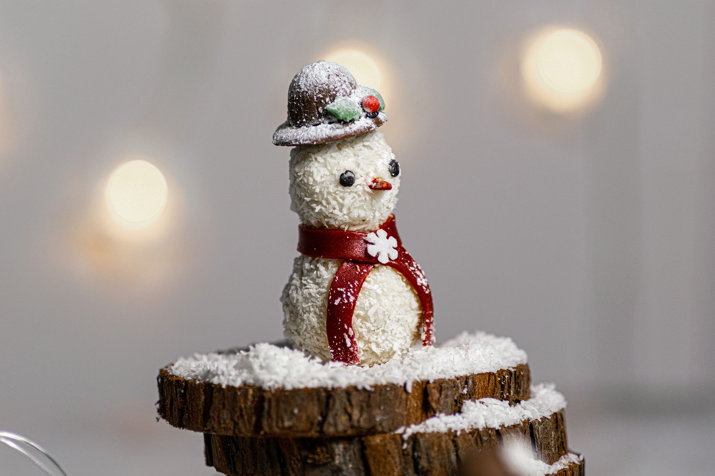 Snowman white chocolate truffle on wooden logs