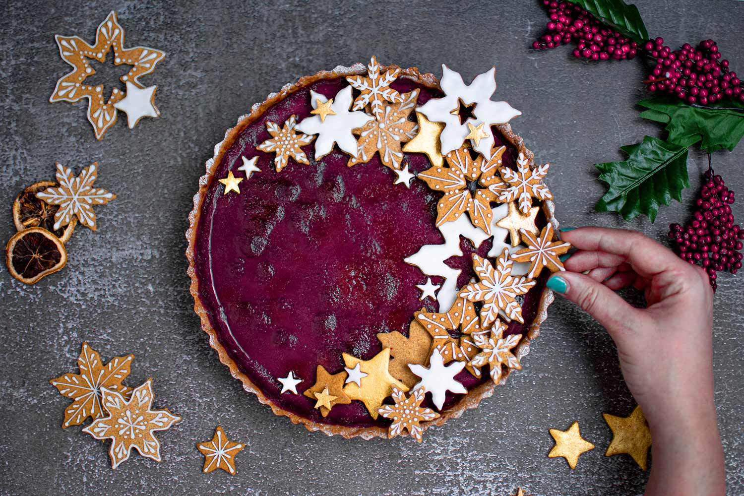 Hand decorating tart with snowflake cookies