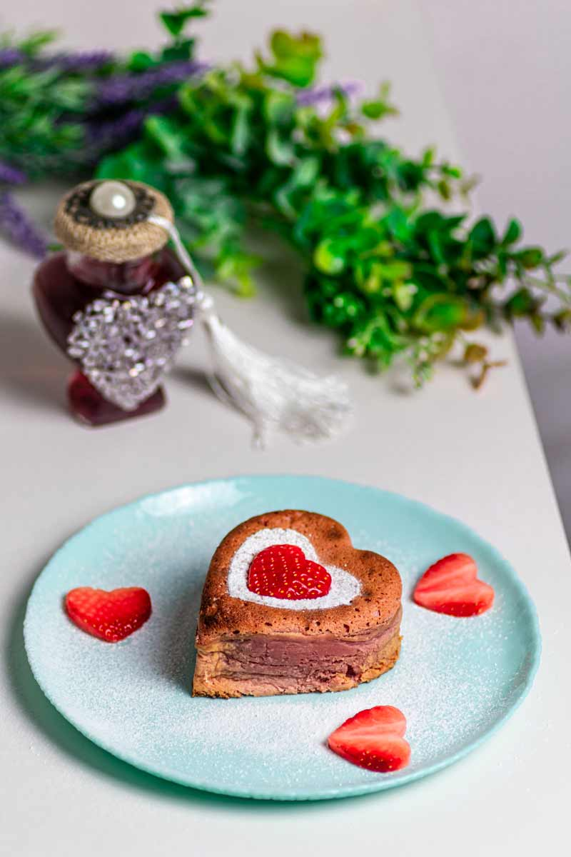 Heart shape lava cake on plate with strawberry hearts