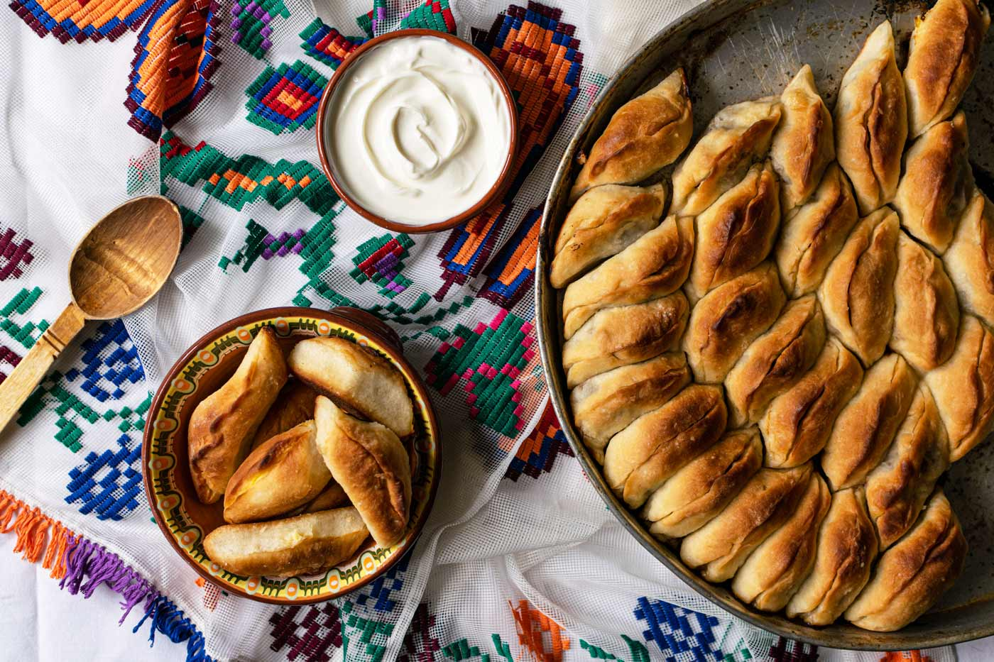 Flatlay view of meat hand pies tray with bowl of yoghurt and smaller dish with hand pies