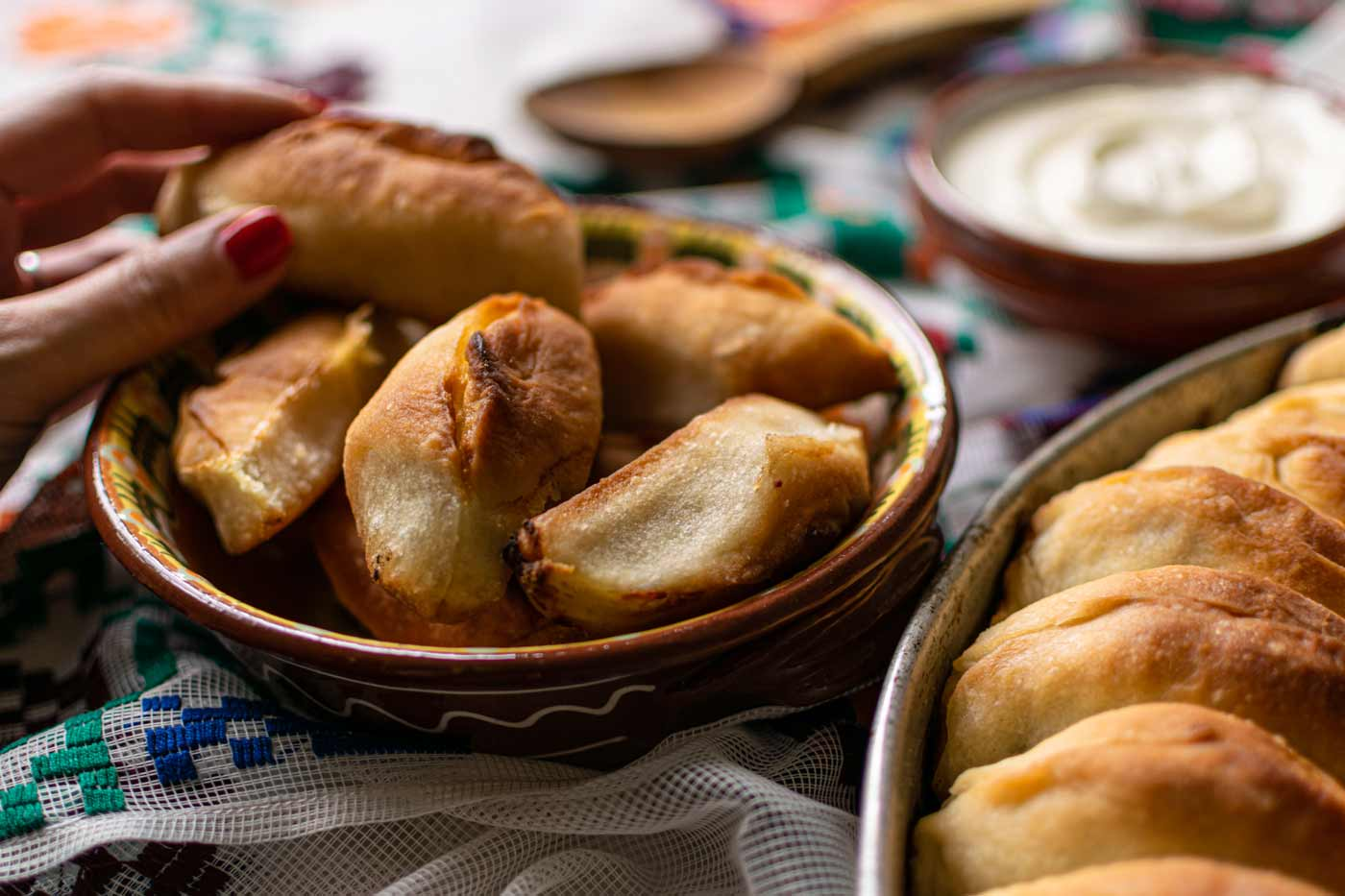 Meat hand pies in bowl with hand reaching for pie