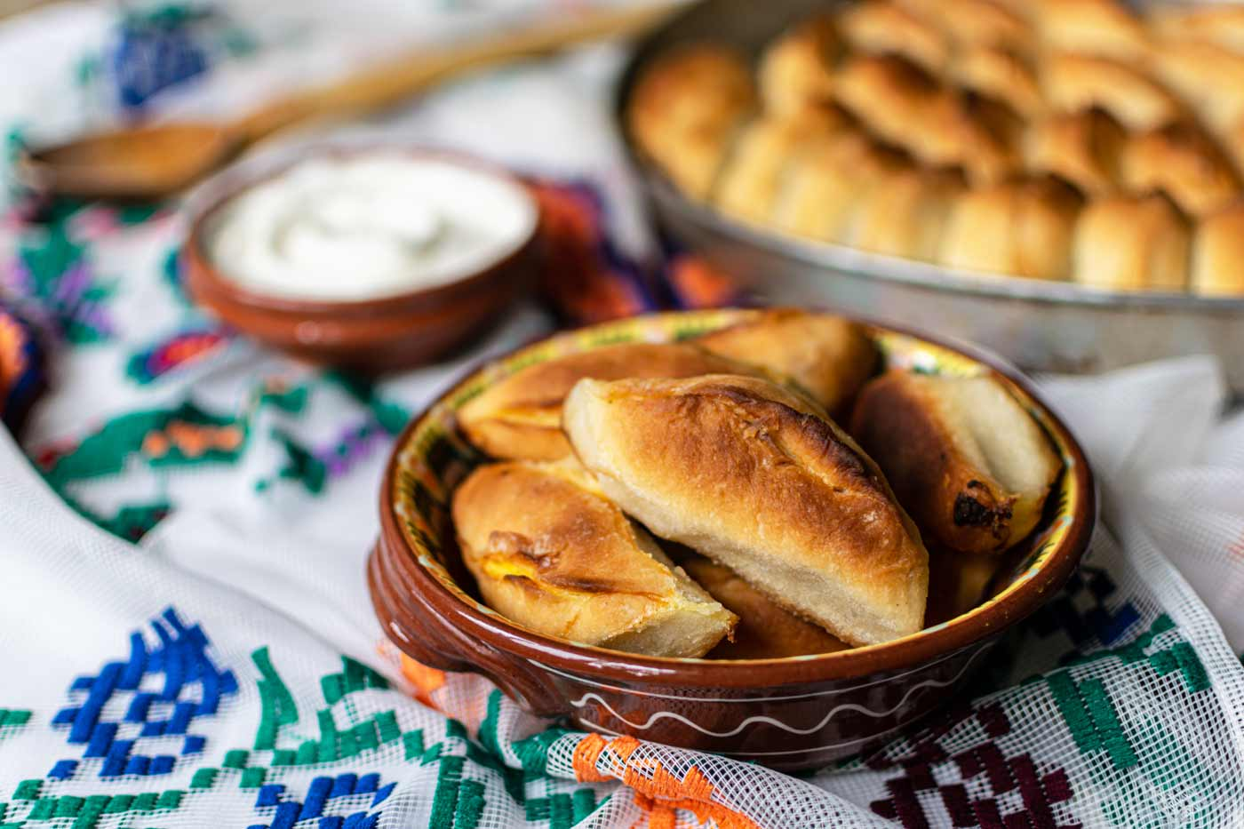 Meat hand pies in bowl with yoghurt and tray in background