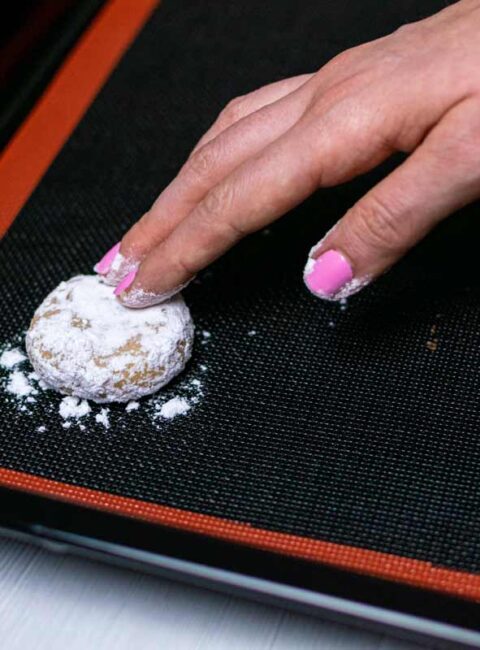 Pressing cookie with hand to flatten