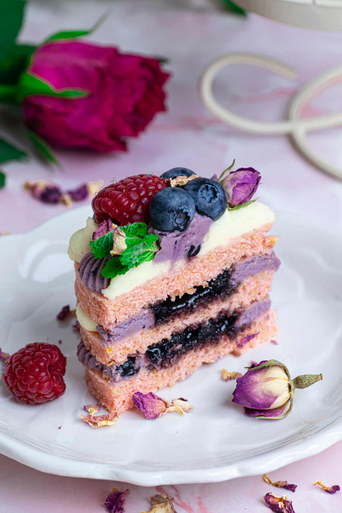Section of mini cake showing interior with cream cheese frosting and blueberry jam
