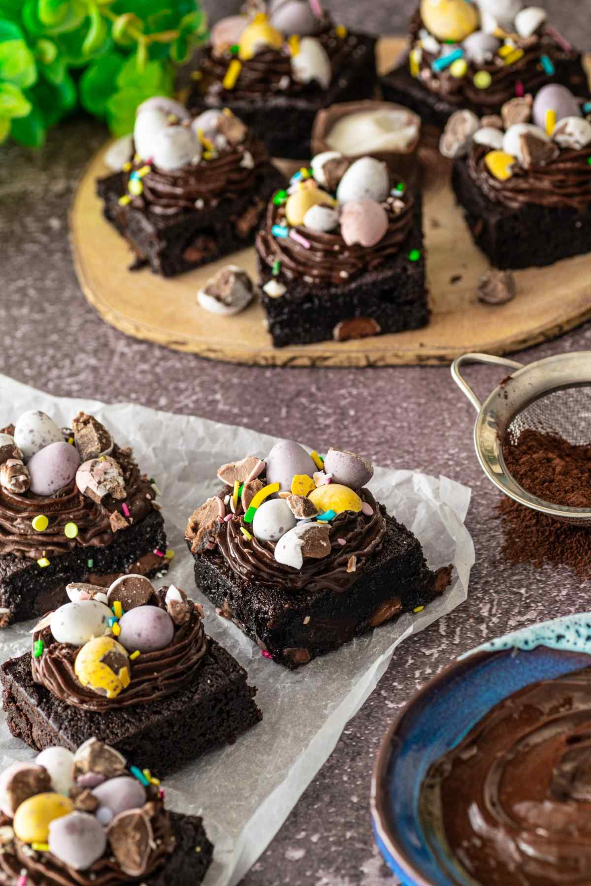 Brownies on baking paper next to sieve with cocoa powder