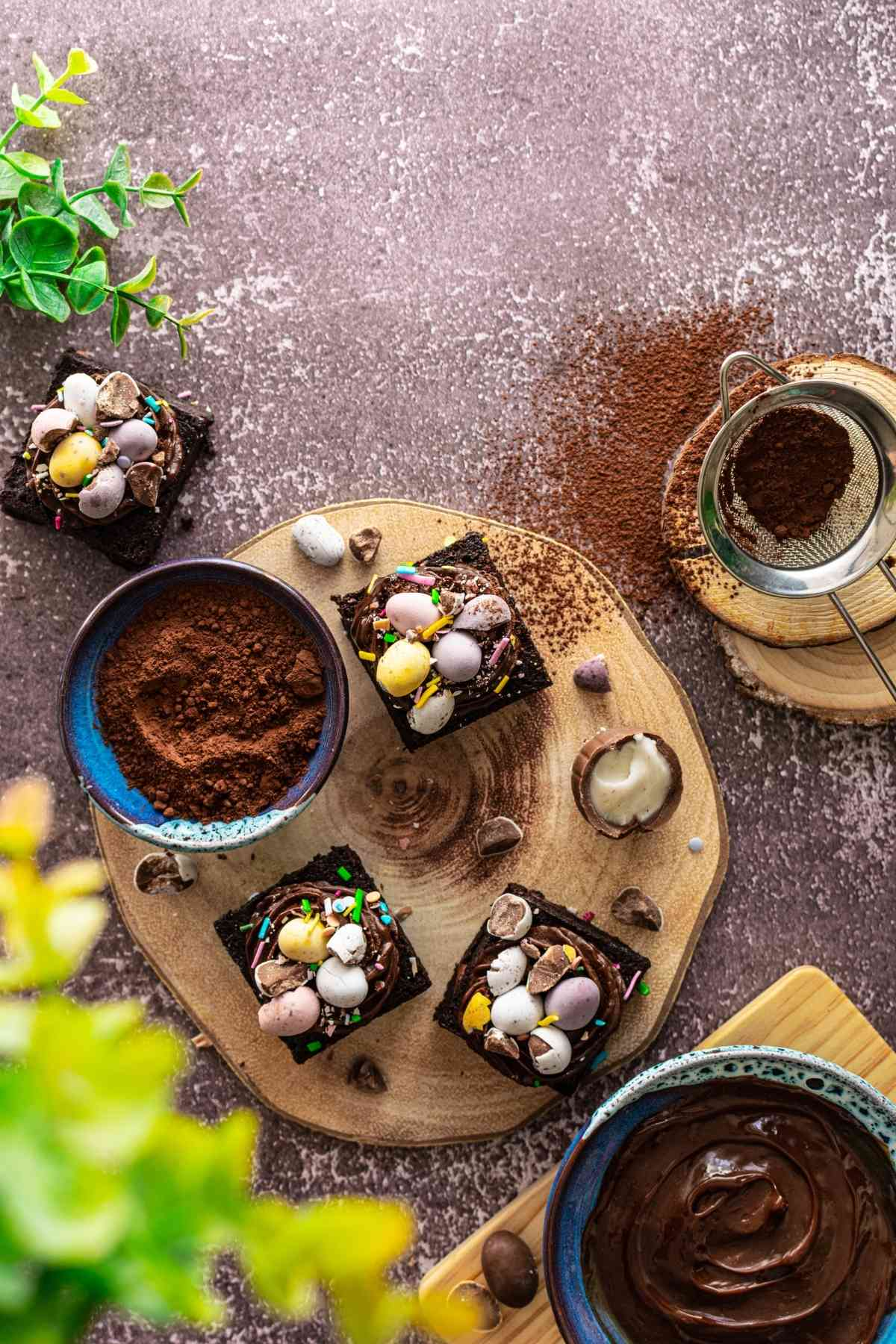 Flatlay of mini egg chocolate brownies on platter with chocolate ganache and cocoa powder
