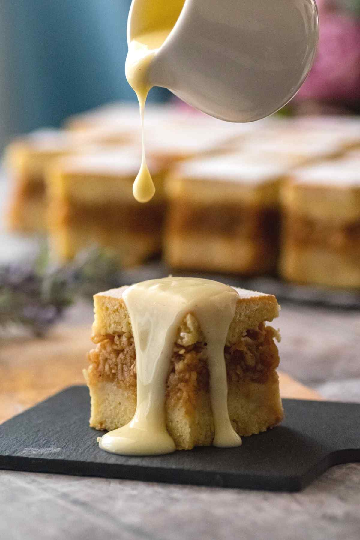 Drizzling pastry cream over slice of apple cake