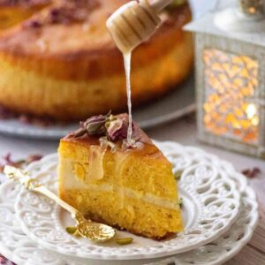 Slice of basbousa cake with honey drizzling over it