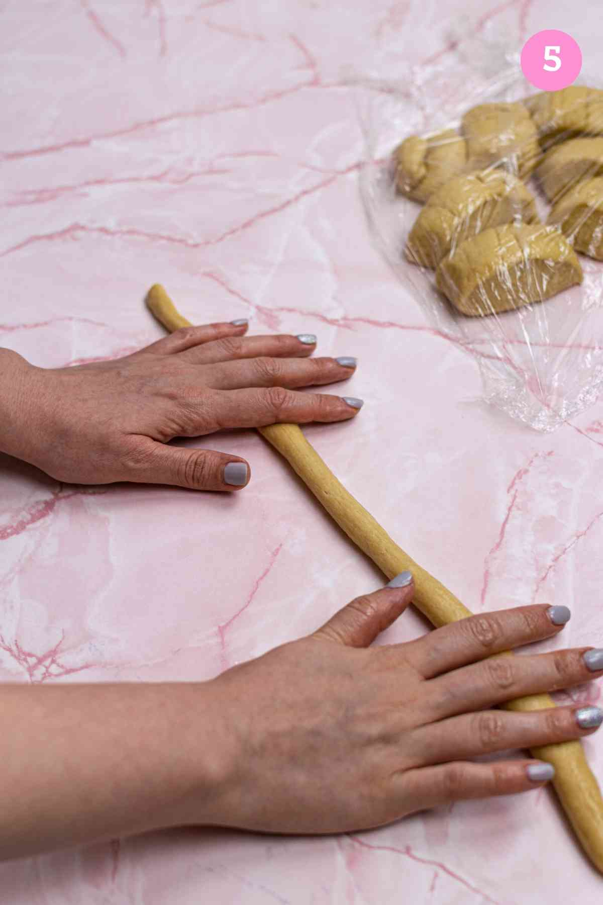 Hands rolling out dough into thin strip