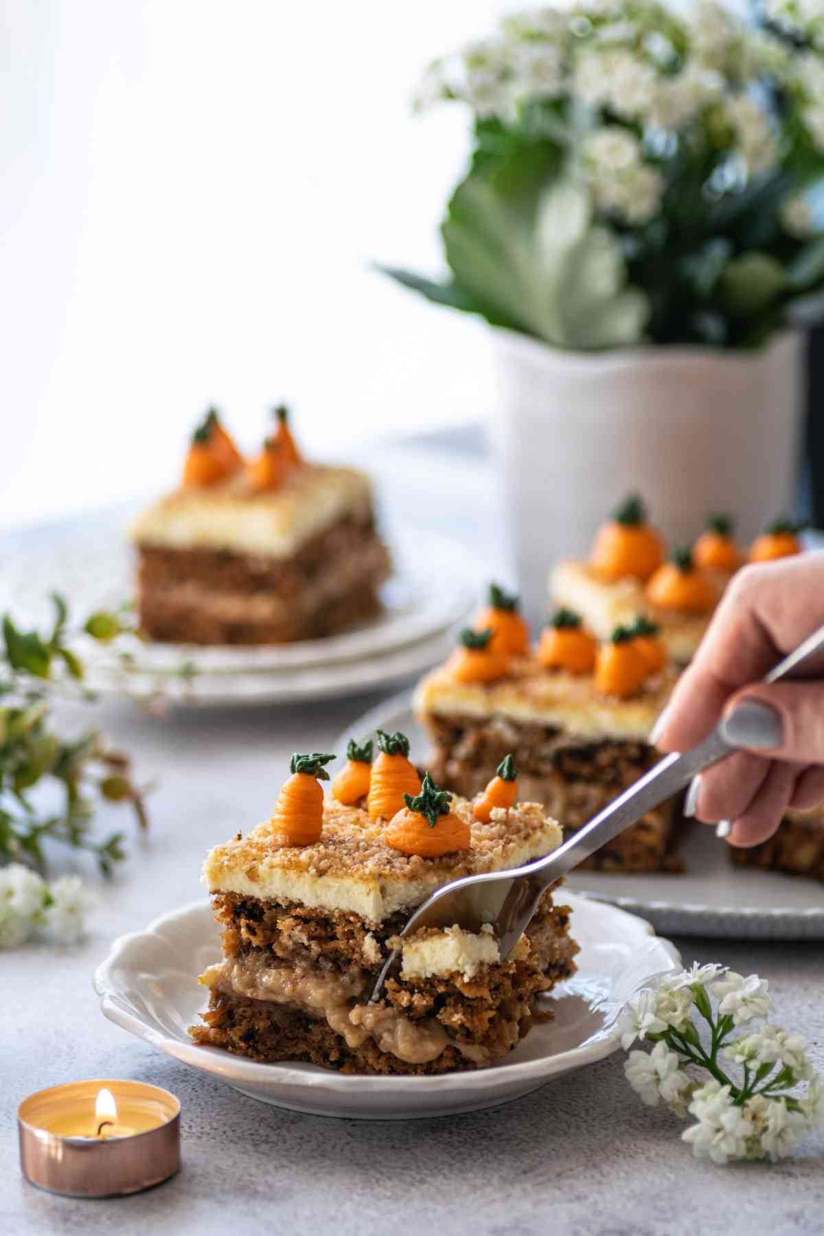 Slice of double layer carrot cake with hand holding fork