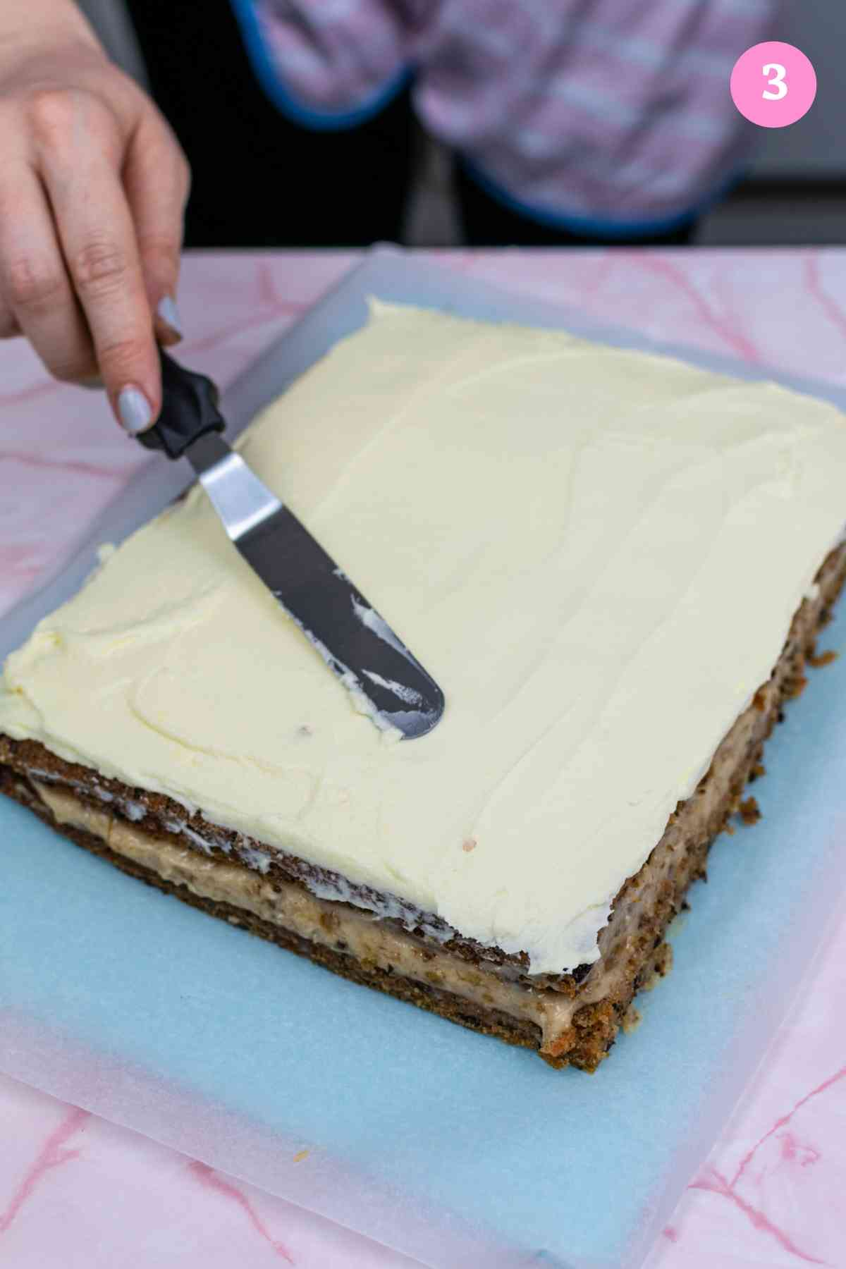 Spreading cream cheese frosting over the double layer carrot cake