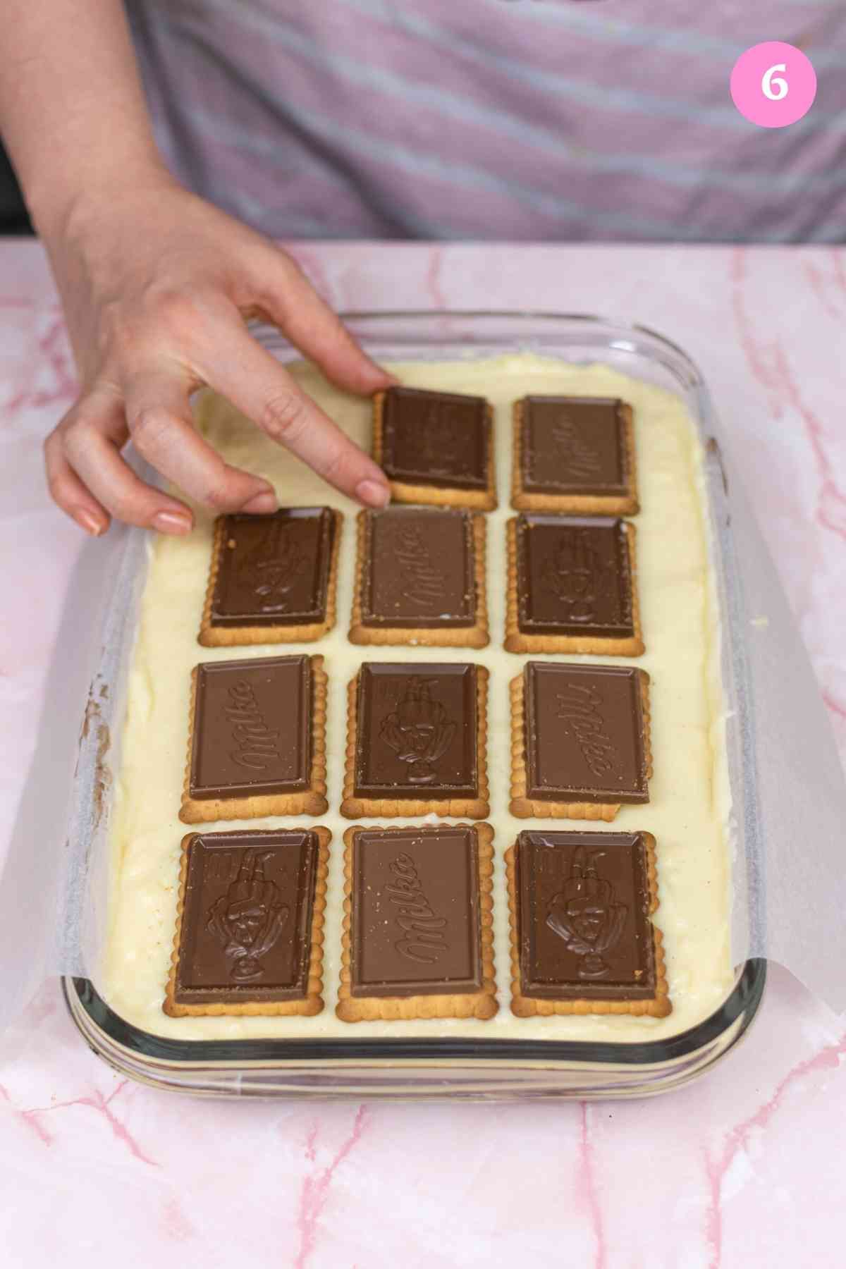 Adding the top layer of chocolate covered biscuits over the vanilla custard layer