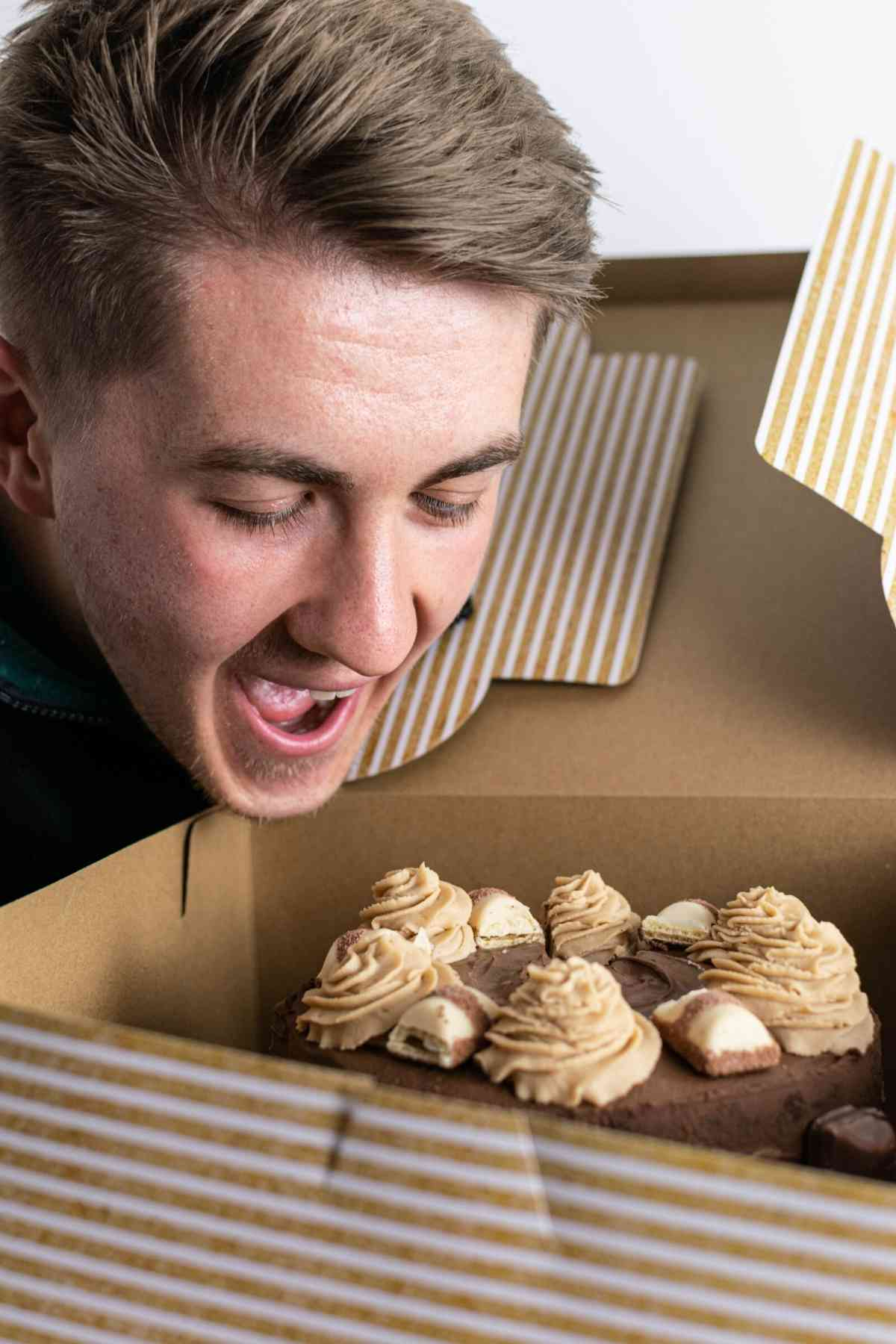 Man pretending to eat cake from above with mouth open