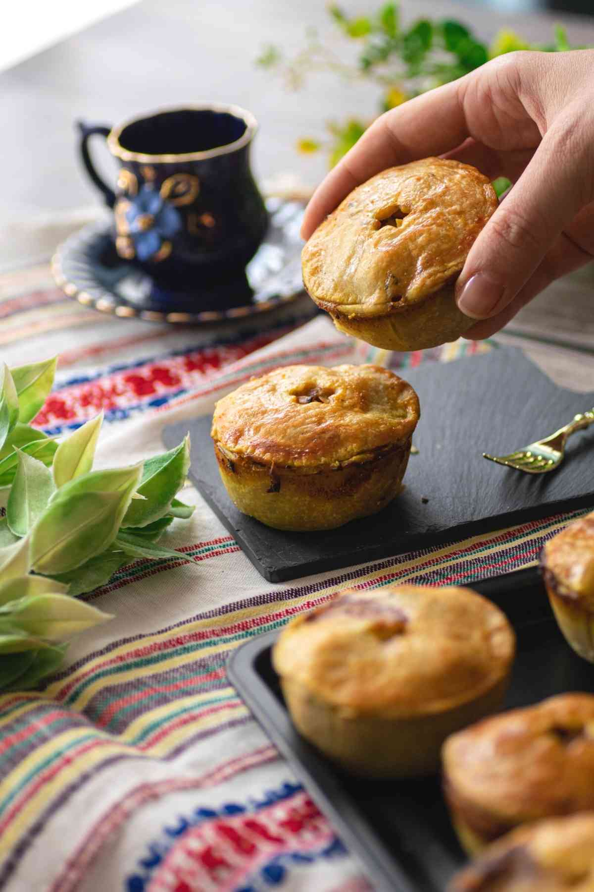 Holding mini Moroccan chicken pie off the platter