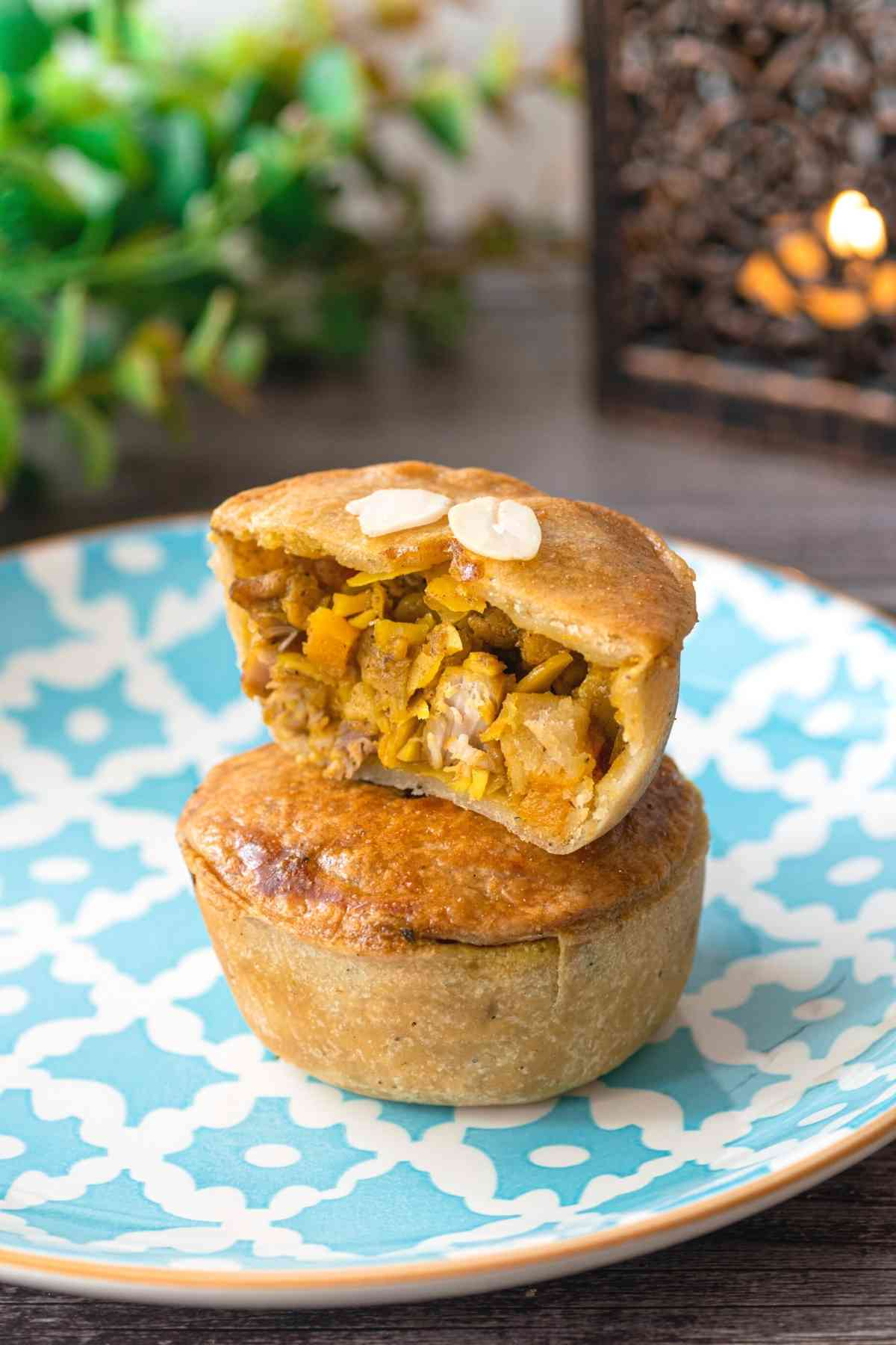 Two mini chicken pot pies stacked with top pie cross section showing filling on Moroccan tile plate