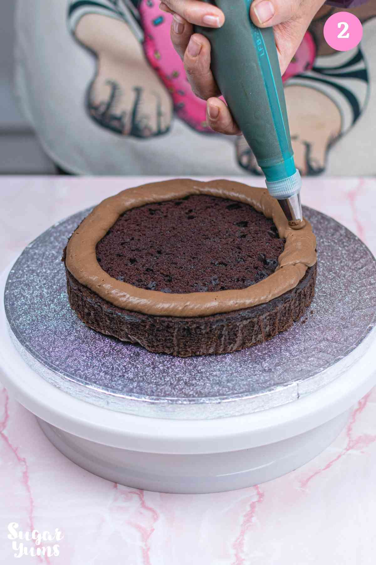 Piping chocolate ganache ring on top of sponge