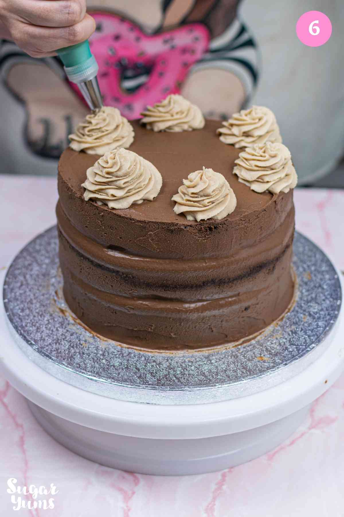 Piping dollops of ganache on the top of the cake with piping bag
