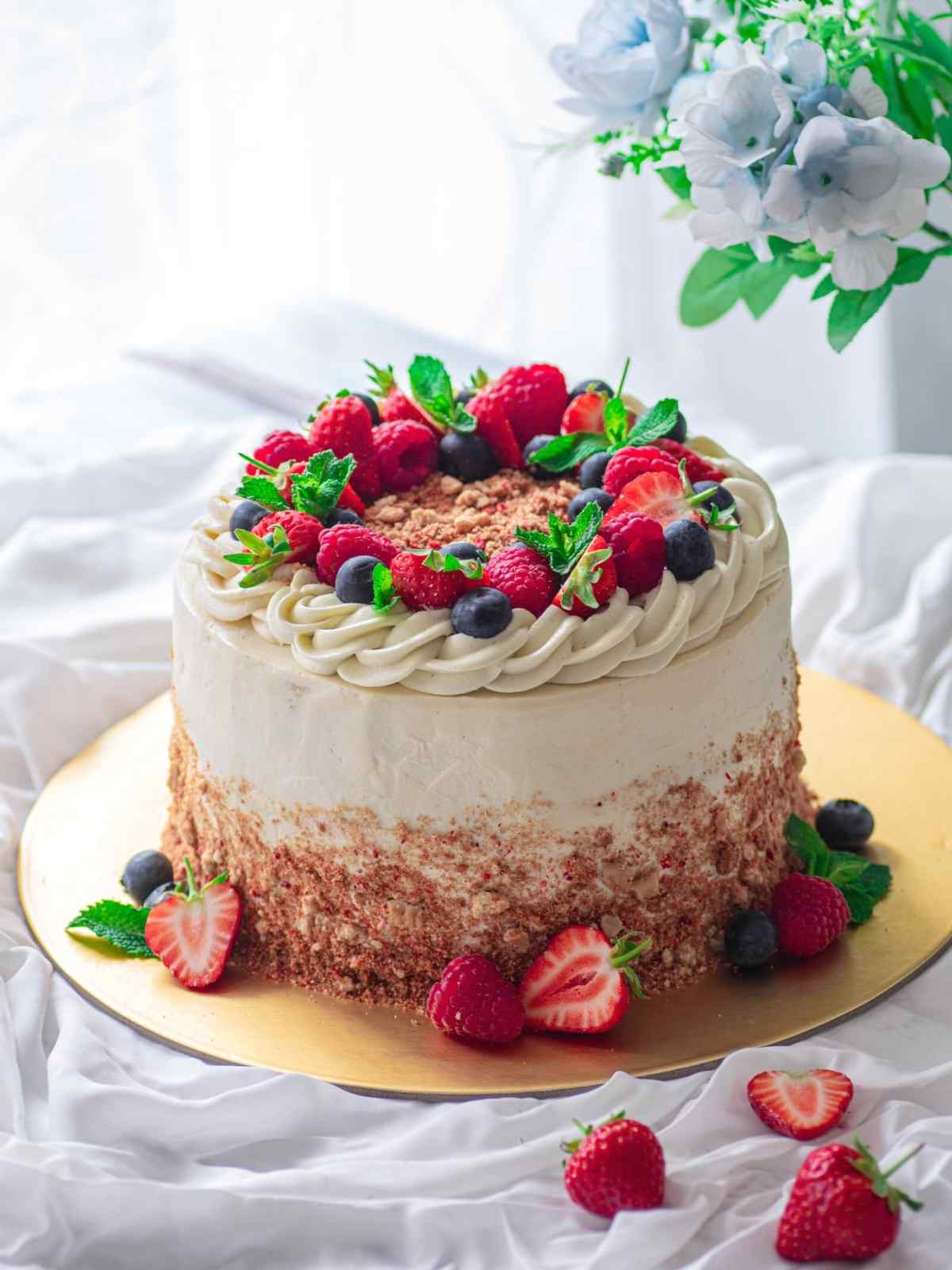 Strawberry cheesecake cake decorated with berries on golden platter and white background