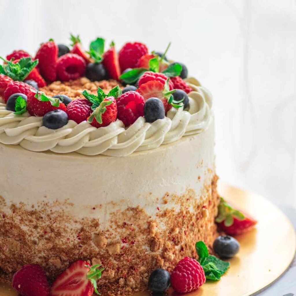 Strawberry shortcake cake decorated with berries with more berries at the base