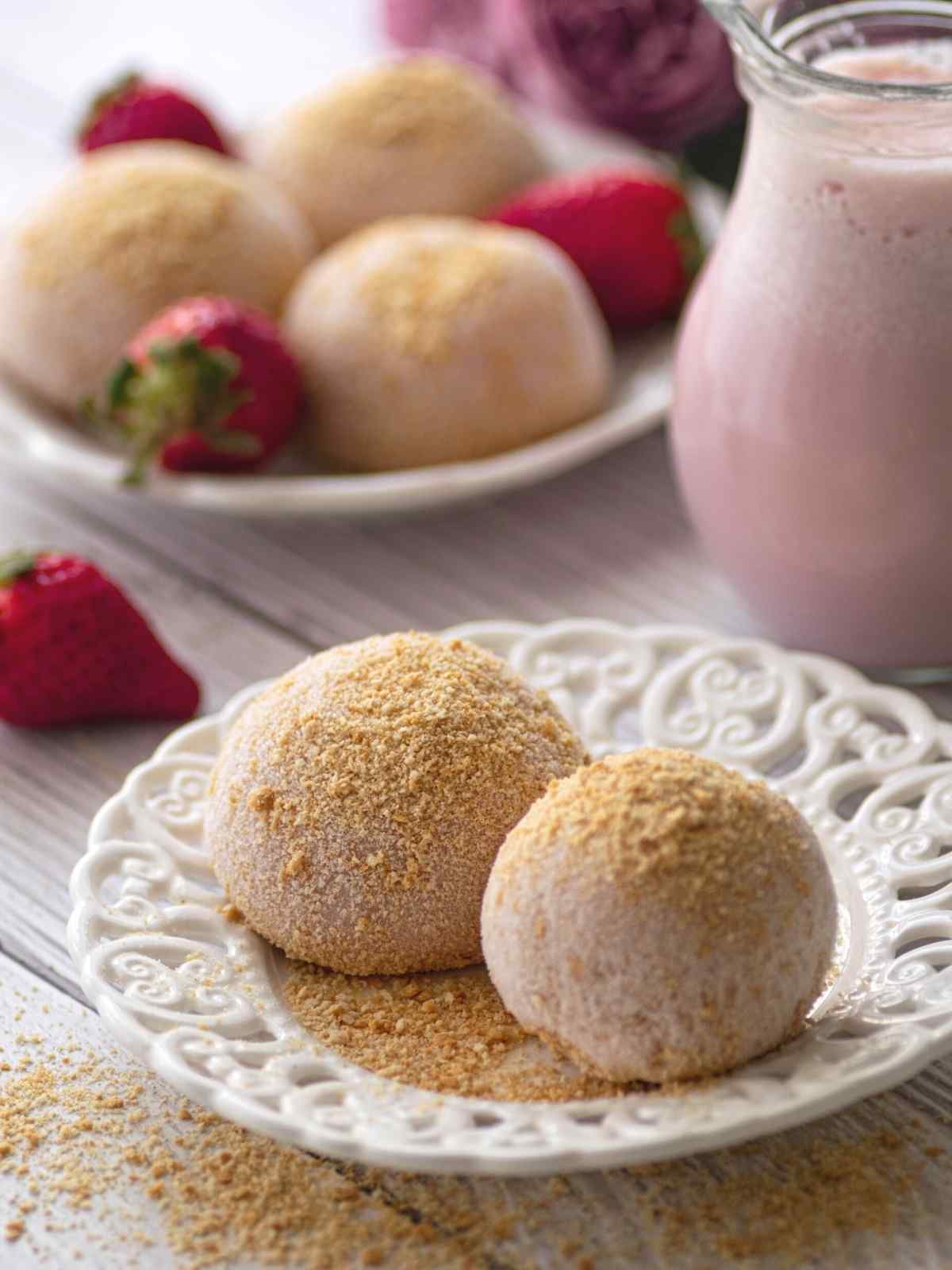 Two strawberry cheesecake mochi on a white plate with biscuit crumbs around