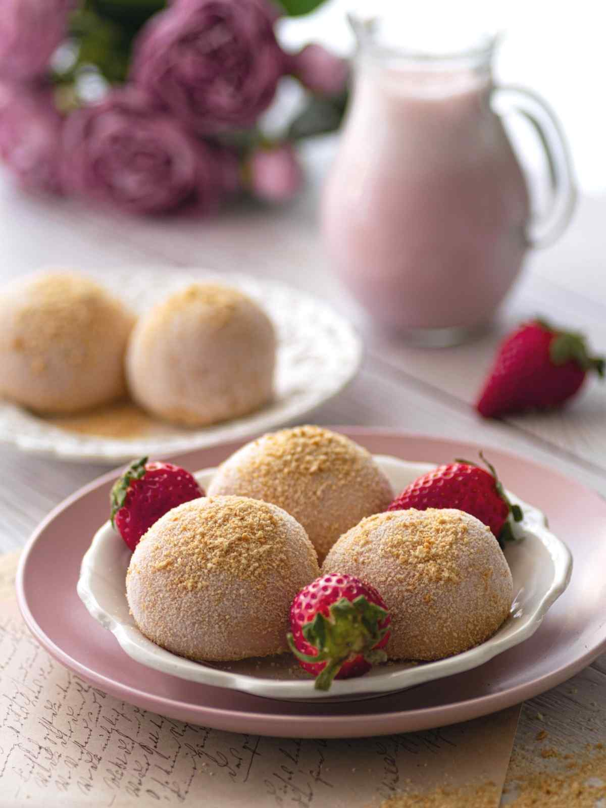 Three strawberry cheesecake mochi on a white plate with strawberries in between the mochi