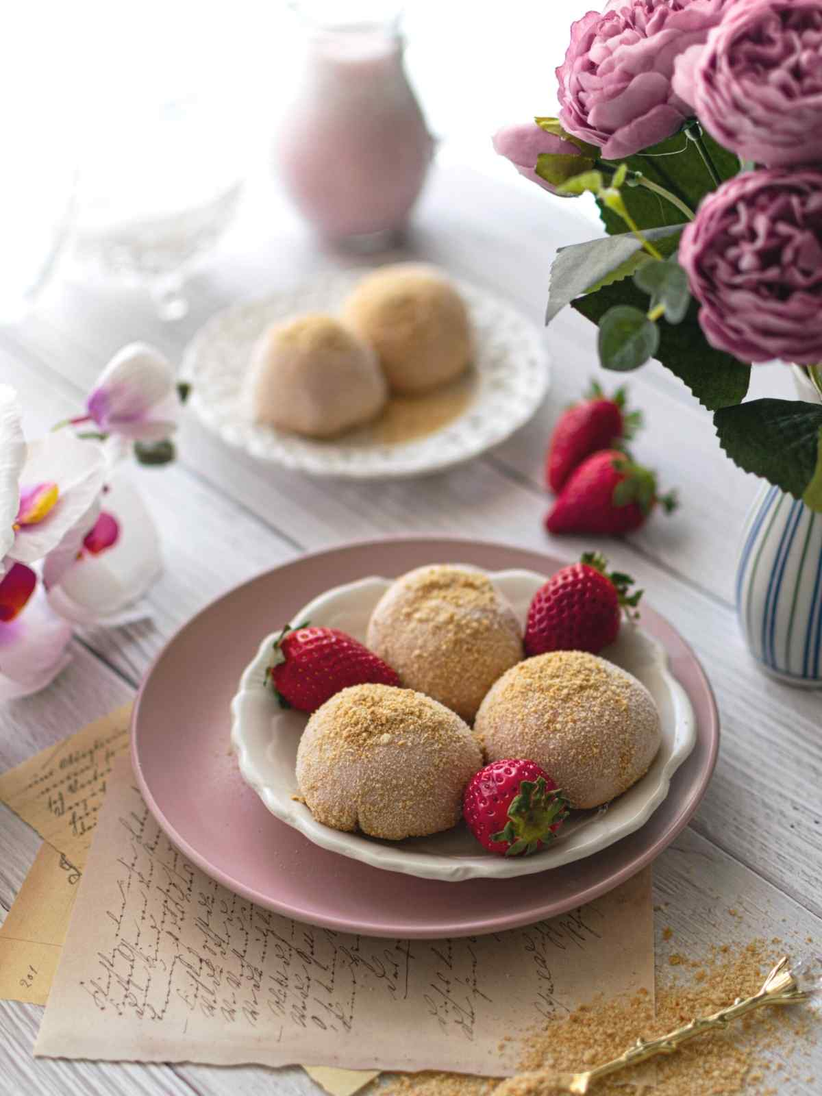 Three mochi on a plate with strawberries and mochi in the background