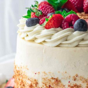 Close-up of cream cheese frosting piped in swirly pattern on cake, decorated with berries