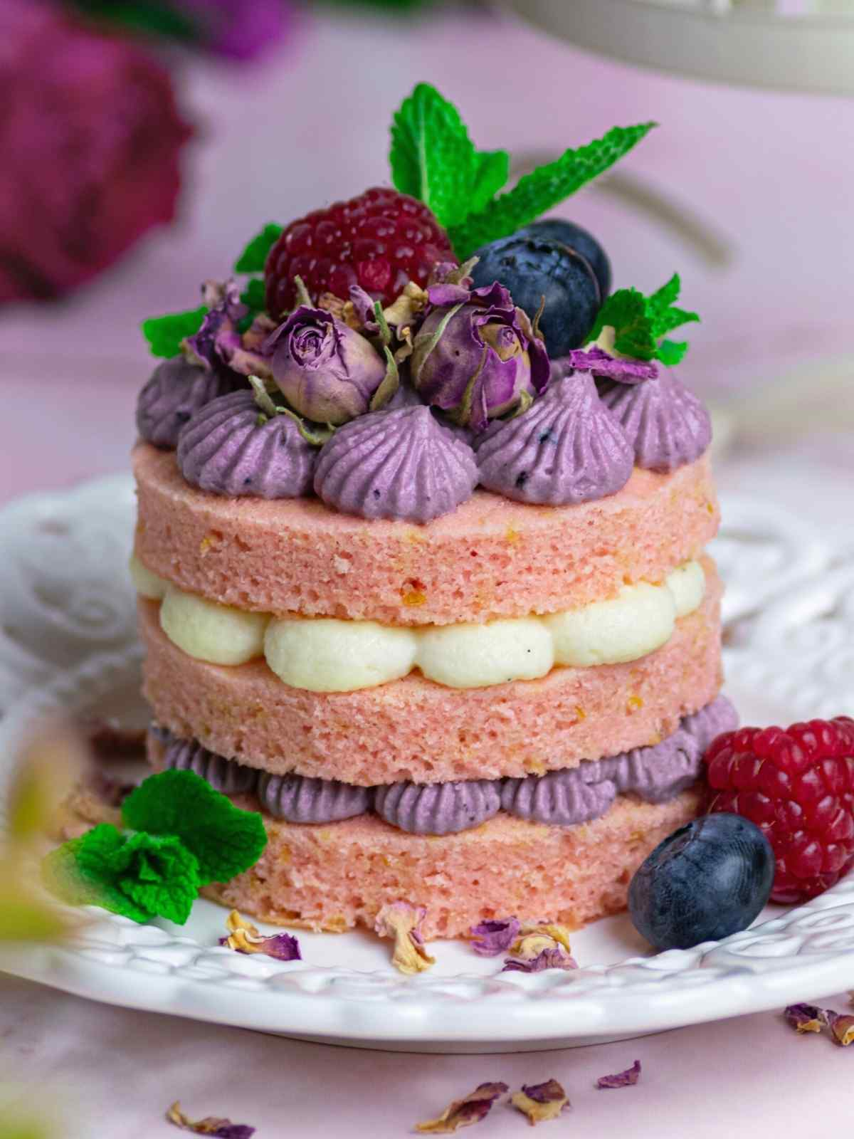 Mini cake with cream cheese frosting between the layers decorated with fresh fruit