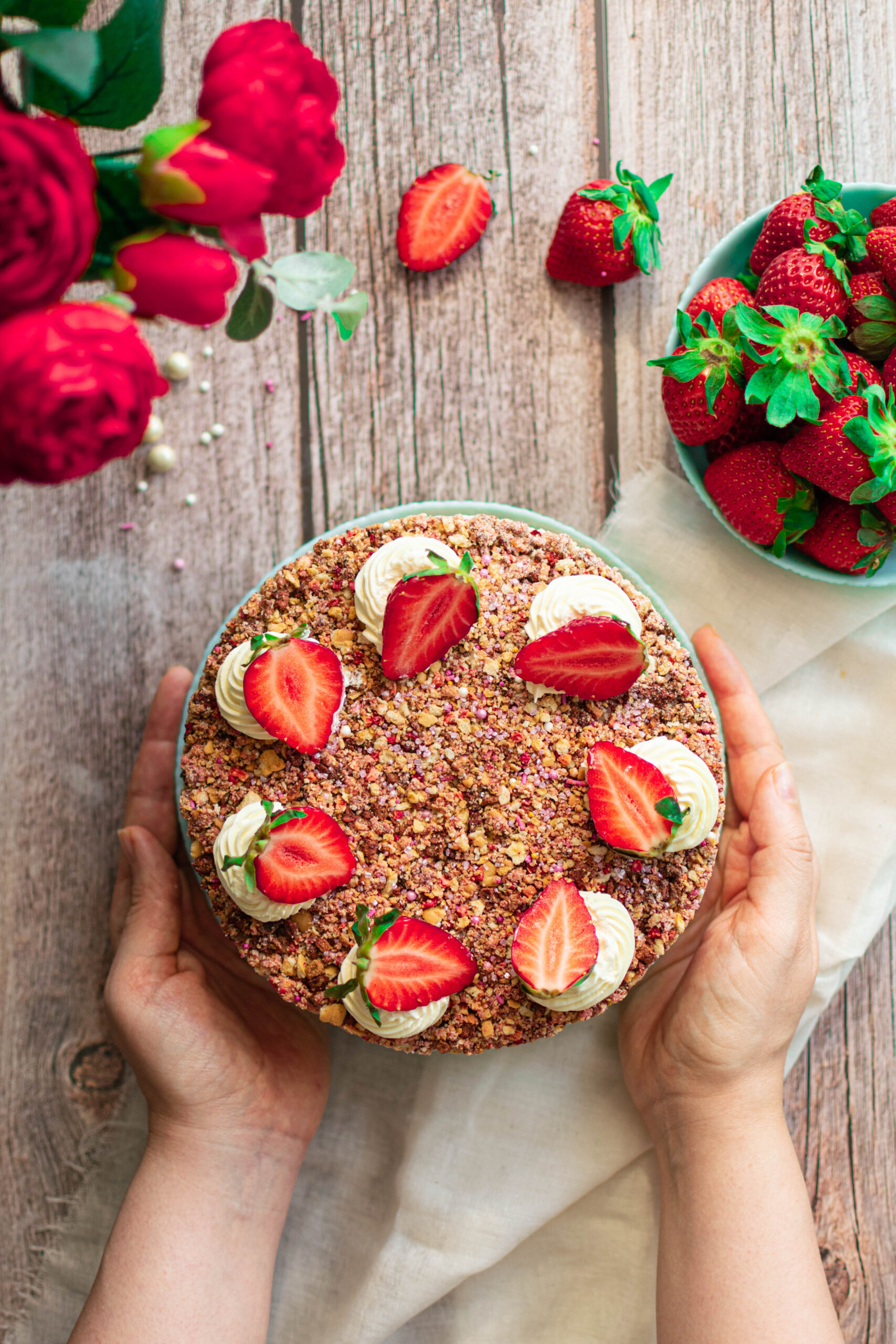 Flatlay image of hands holding strawberry crunch cheesecake