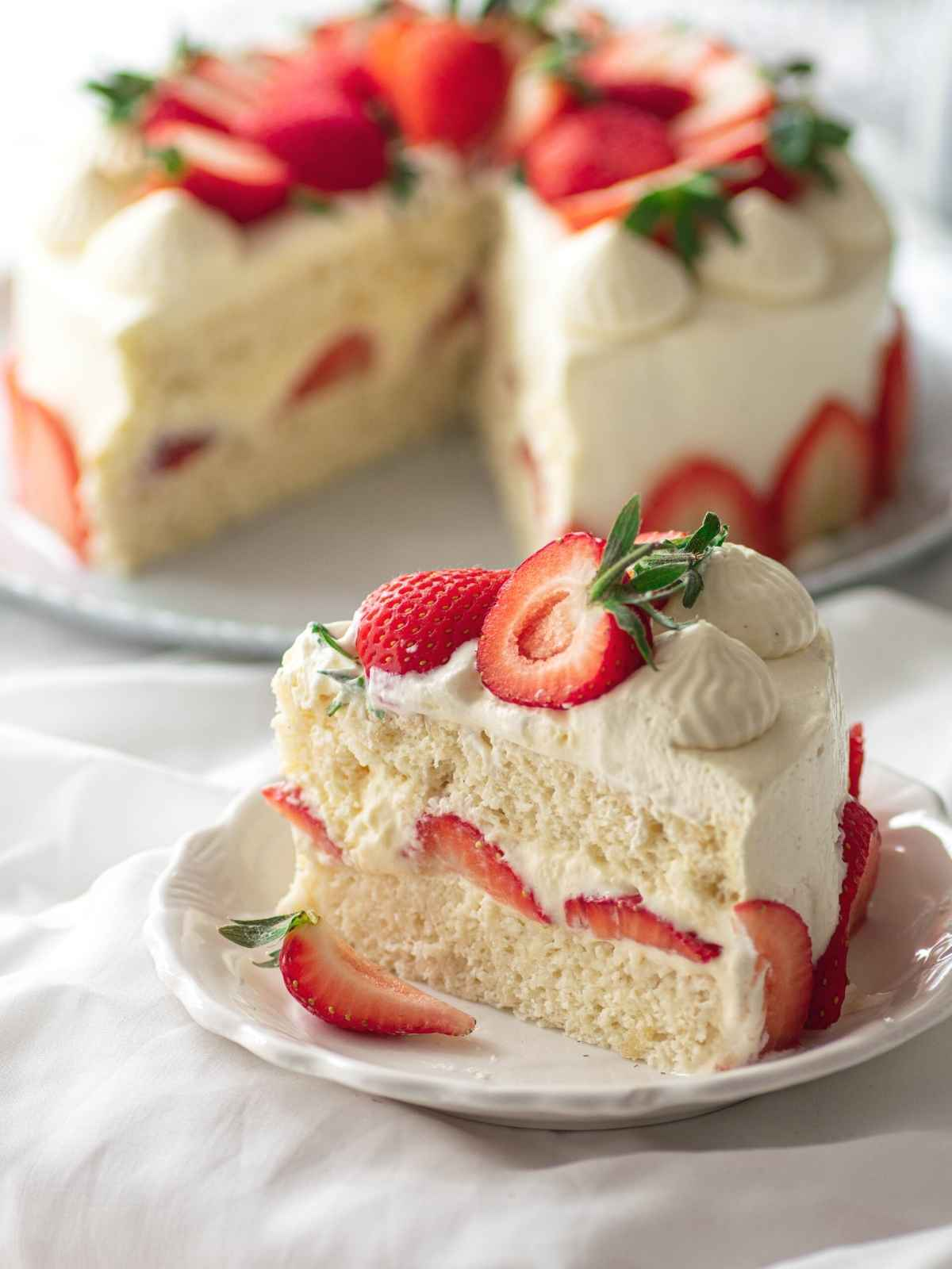 Slice of Japanese strawberry shortcake on plate with full cake in the background