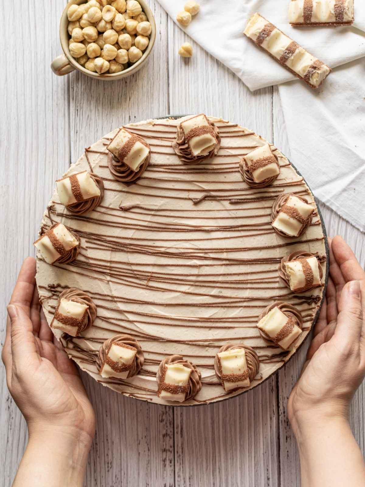 Flatlay image of hands holding plate of Kinder Bueno cheesecake
