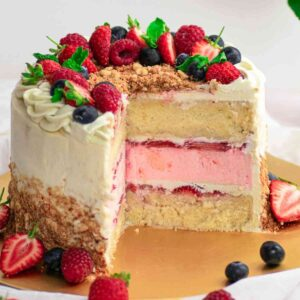 Strawberry cake on golden platter with slice cut out