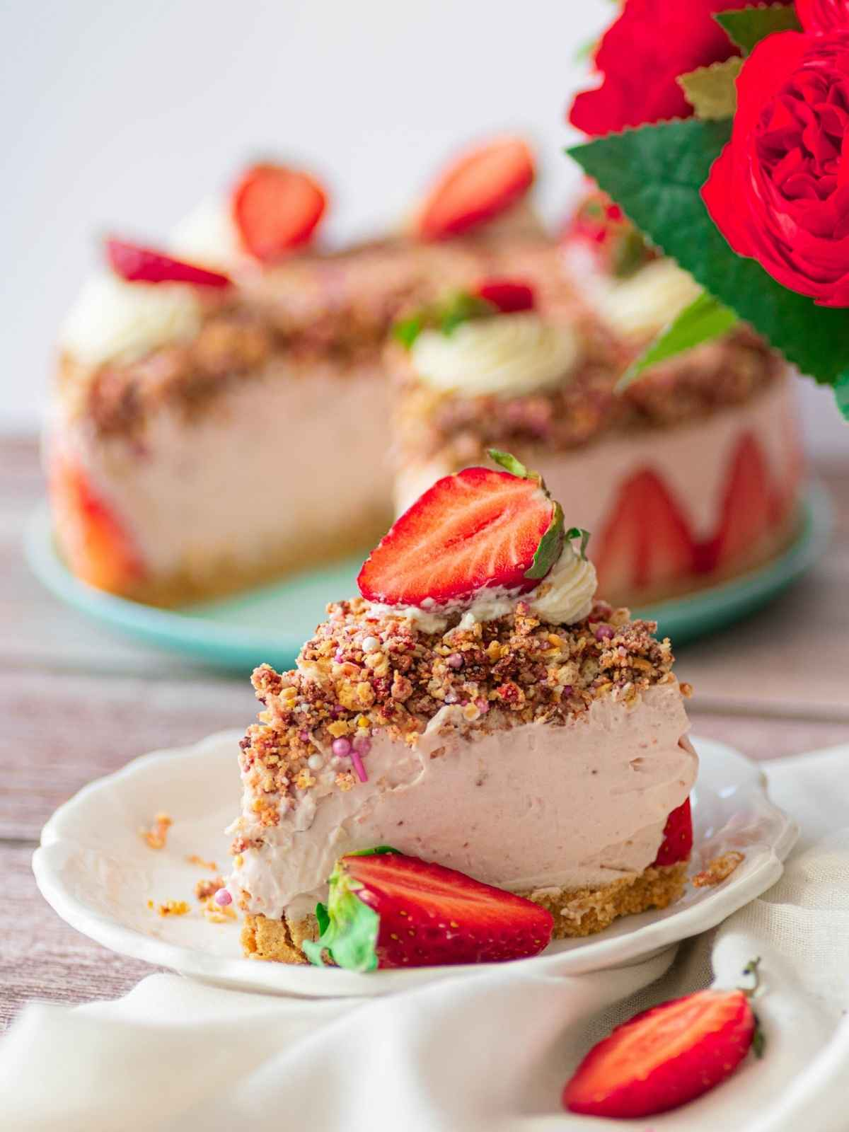 Slice of strawberry crunch cheesecake on white plate
