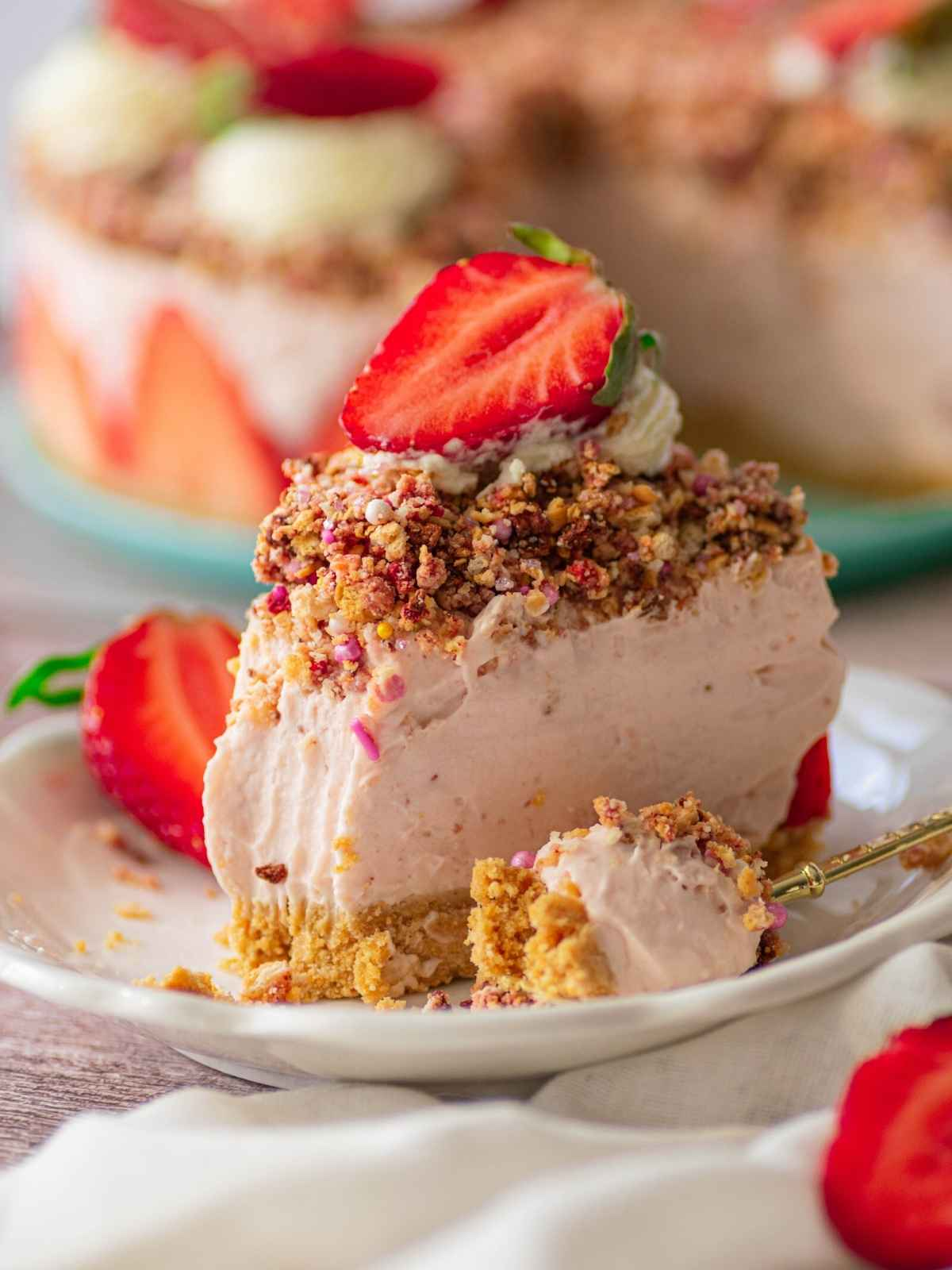 Closeup of slice of strawberry crunch cheesecake on white plate
